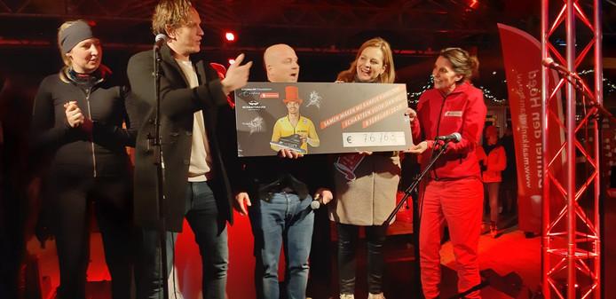 Directeur Tijs Nederlof van Schaatsbaan Rotterdam (tweede van links) en directeur Leonore Tuijt van het Daniel den Hoed fonds (rechts) met de cheque.