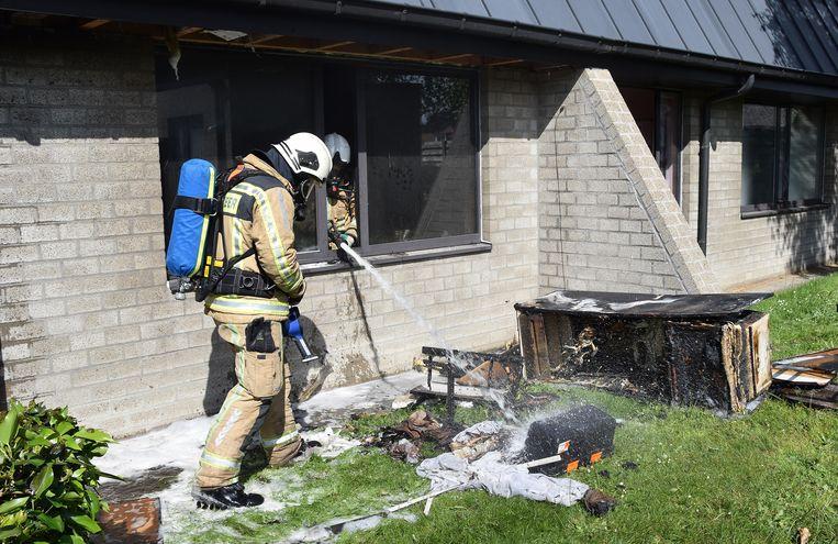 De brandweer aan het werk aan de woning.
