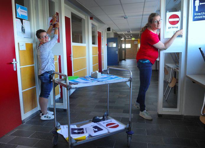 Concierges Janet Luitwieler (links) en Aimee Schaeffer van CSW zijn druk bezig met stickers plakken in de gangen en lokalen.