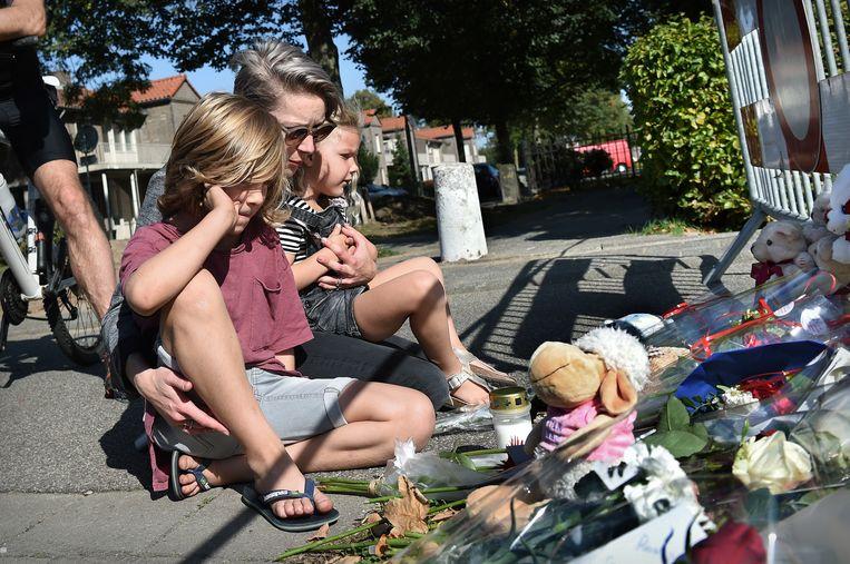 Een moeder en haar twee kinderen hebben juist bloemen gelegd achter de afzetting bij de plek van het ongeval. Ze nemen nog even een moment van stilte.  Beeld null