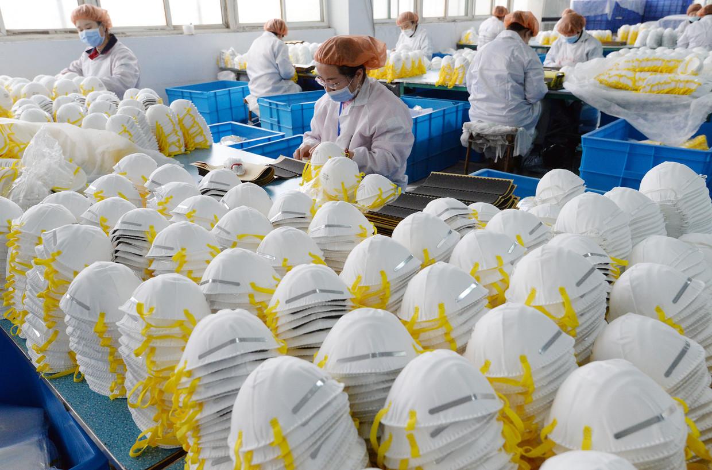 In een Chinese fabriek worden mondkapjes gemaakt. Veel landen, zowel binnen de Europese Unie als daarbuiten, zijn van de Chinese productie afhankelijk.  Beeld null