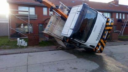 Vrachtwagen met liftarm kantelt tijdens overbrengen van bouwmaterialen