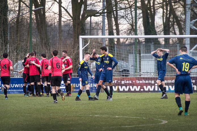 De spelers van Roda'28 (links) vieren een treffer in de derby, terwijl die van Ewijk balen.