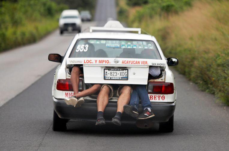 Migranten in de achterbak van een taxi in de staat Veracruz.