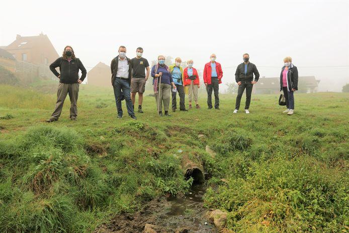 Buurtbewoners en gemeenteraadsleden van N-VA bij één van de buizen op de beek waar liters afvalwater door geloosd wordt richting natuurgebied Oude Zenne.