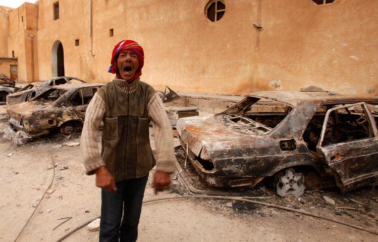 Een man bij uitgebrande auto's bij een regeringsgebouw in Tobruk, in 2011. Beeld REUTERS