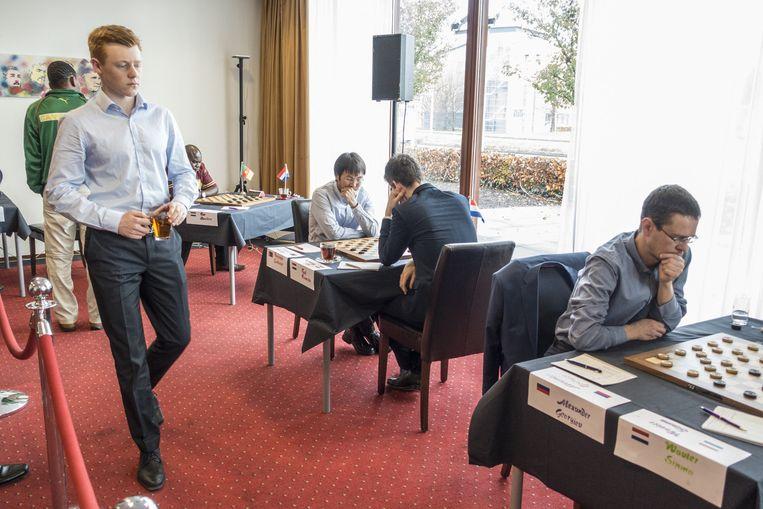De hoofdrolspelers. Jan Groenendijk loopt terug naar zijn bord. Op de rug gezien en in blauw jasje Roel Boomstra. Rechts wereldkampioen Alexander Georgiev. Beeld  Harry Cock / de Volkskrant