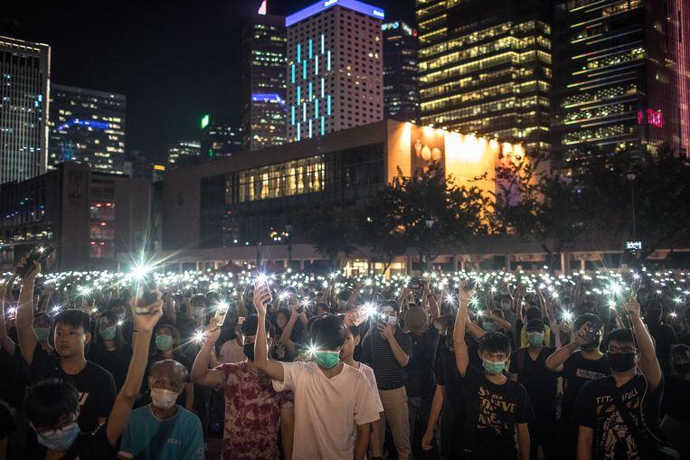 Studenten zwaaien met het lichtje van hun telefoon tijdens een anti-regeringsprotest in Hongkong.