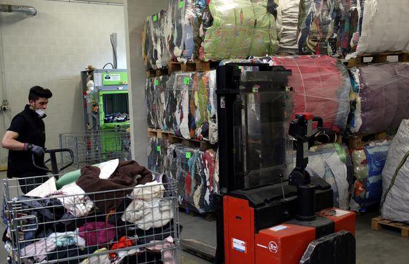 Een medewerker van Den Azalee bij het sorteren en verwerken van ingezameld textiel.