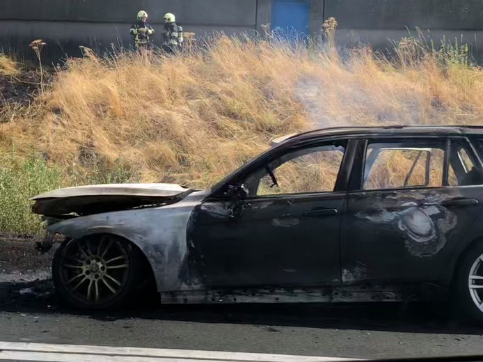 Brandende auto langs de A50 in de berm.