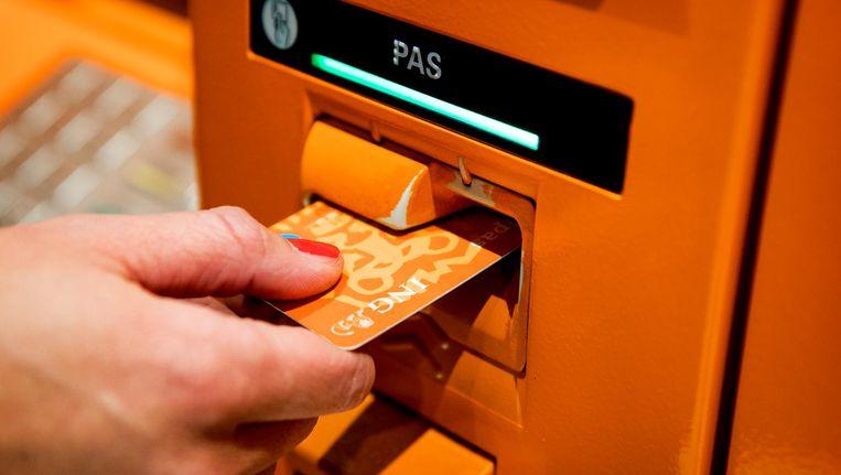 Een klant gebruikt een pinautomaat van de ING bank. Beeld anp