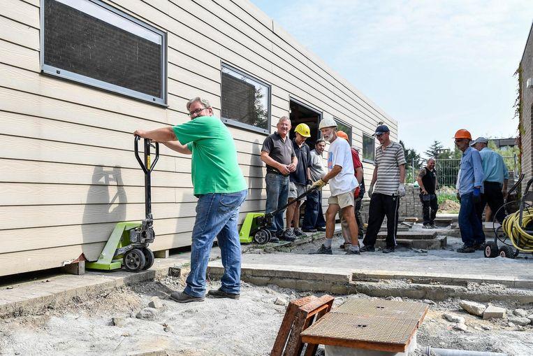 Vrijwilligers van vzw Eindelijk verplaatsen de grote tuinberging.