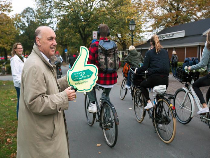 Tom de Bruijn steekt zijn duim omhoog om fietsers aan te moedigen.