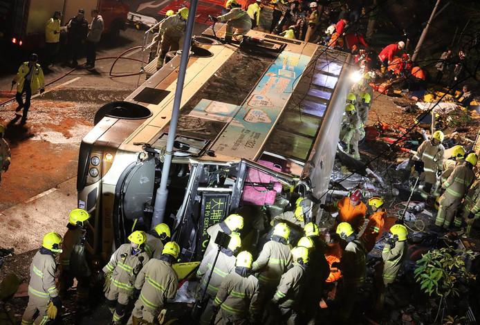 Bij een busongeluk met een dubbeldeksbus in Hongkong zijn zeker negentien doden en veertig gewonden gevallen. Door nog onbekende oorzaak kwam de dubbeldekker op z'n kant terecht. Foto SCMP