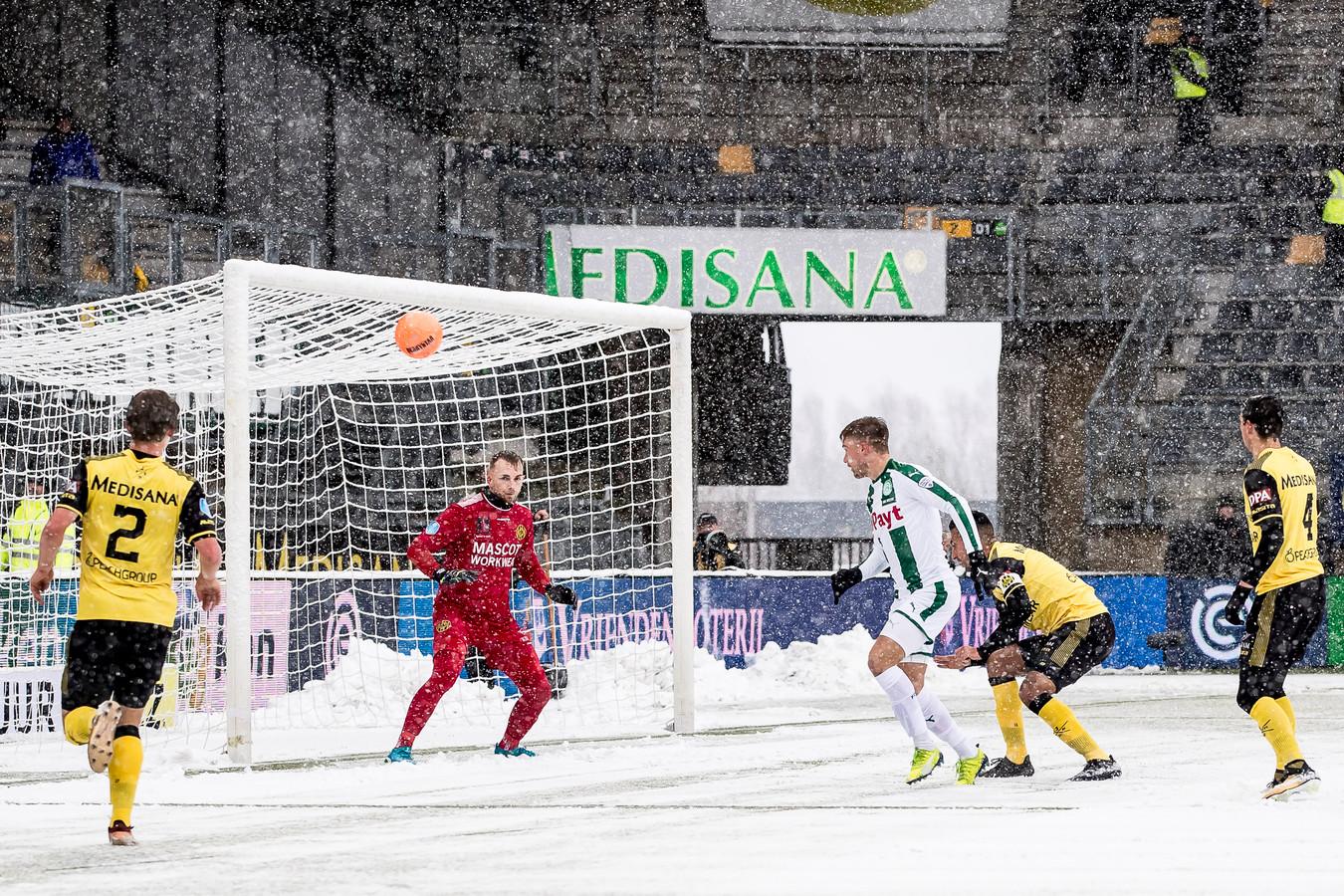 Roda JC - FC Groningen, De wedstrijd in het Parkstad Limburg Stadion ging met af en toe sneeuwvrij maken van het veld gewoon door. Hier een kans voor FC Groningen speler Tom van Weert (M), Roda JC keeper Hidde Jurjus (2L)