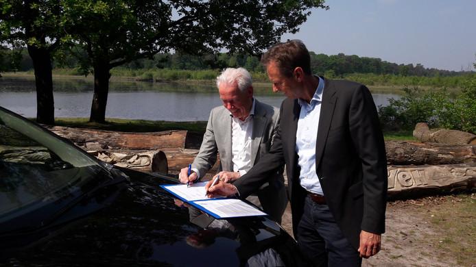 Burgemeester Peter Maas (links) en Marc de Wit van de provincie tekenen de overeenkomst op de motorkap van een auto van Staatsbosbeheer bij het Kroonven in Bladel.