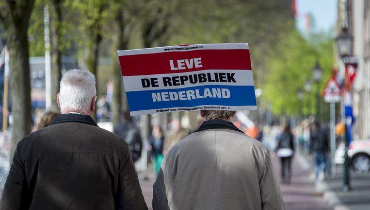 Leden van Het Nieuw Republikeins Genootschap (NRG) staan met een actiebord langs de route op Koningsdag met daarop de tekst 'Leve de republiek Nederland'. Beeld ANP