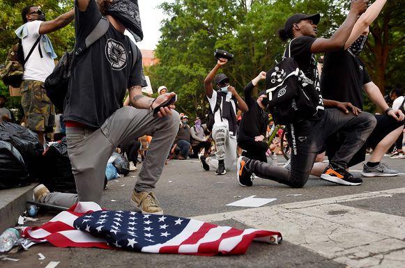 Betogers knielen en ballen hun vuist bij de ingang van Lafayette park dichtbij het Witte Huis. (06/06/2020)