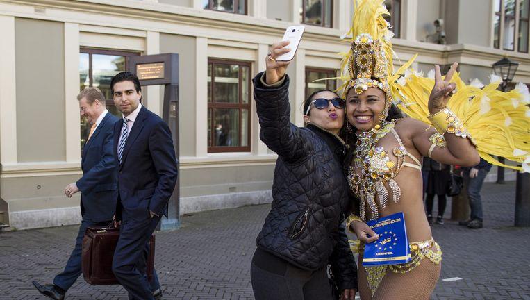 Braziliaanse danseres voert campagne voor het referendum, terwijl minister van Justitie Ard van der Steur langsloopt, 25 september. Beeld Freek van den Bergh