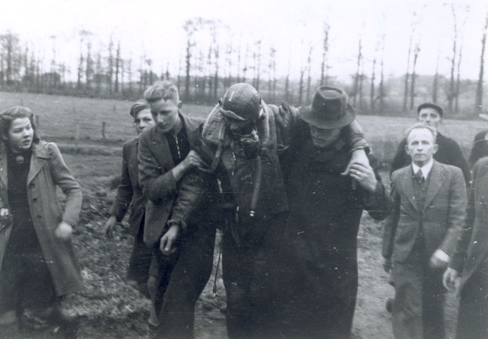 Burgers helpen de Amerikaanse boordschutter Harlan Mann in veiligheid na de crash van zijn bommenwerper op 11 januari 1944 in de omgeving van Berkum.