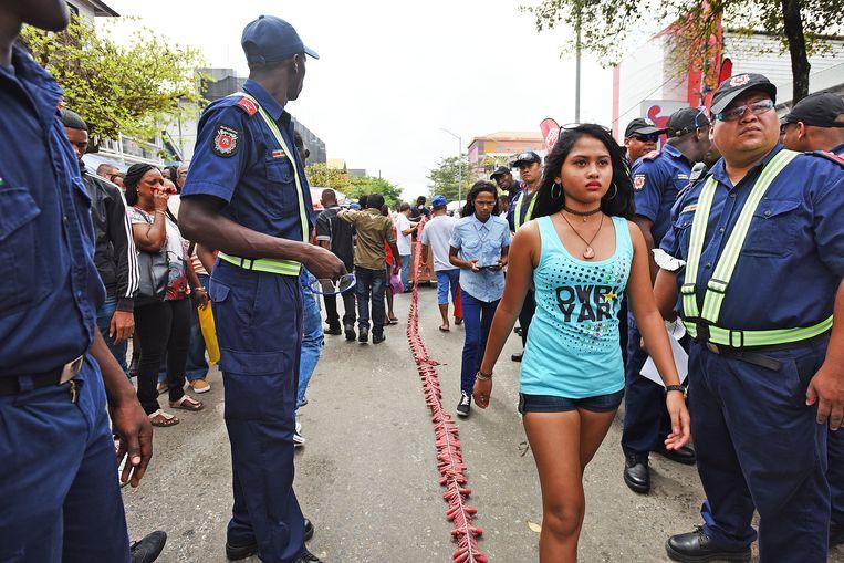 Branweermannen kijken toe hoe de pagara's, lange linten met zware rotjes, in de centrum van Paramaribo worden gelegd. De stad maakt zich op voor het Owruyariviering, inmiddels een begrip. Beeld Guus Dubbelman /  de Volksrkatn