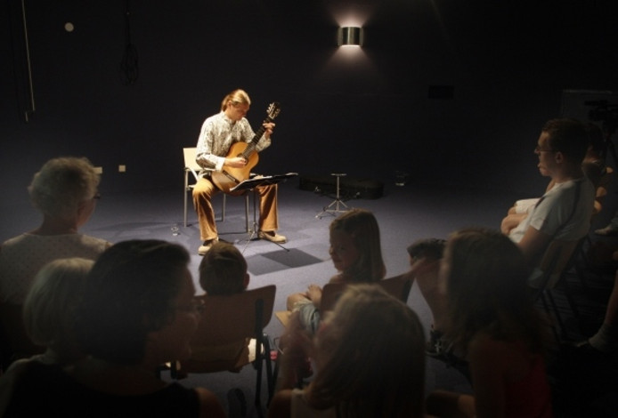 Gert-Jan Adema laat in het bezoekerscentrum van Staatsbosbeheer horen hoe een ree op zijn gitaar klinkt. Foto Cees Baars