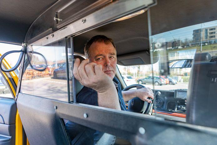 Bruno van der Hoek sluit het luikje van het scherm in zijn New Yorkse yellow cab.