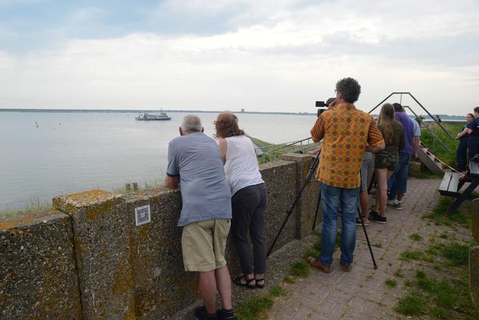 Omstanders bekijken de zoektocht naar de twee vermiste duikers.