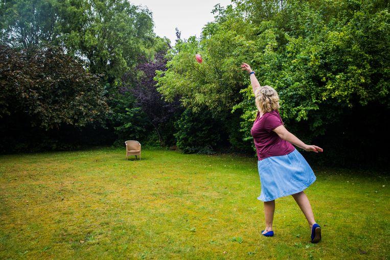 Ann-Sophie Claeys demonstreert het discuswerpen in haar tuin