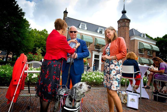 Omdat wethouder Judith Bokhove (midden) de koninklijke versierselen in verband met de coronaregels niet mag opspelden bij Bob Uitjens, doet zijn vrouw Annemarie het. In de tuin van het Charloise landhuis de Oliphant werden twaalf mensen gedecoreerd.