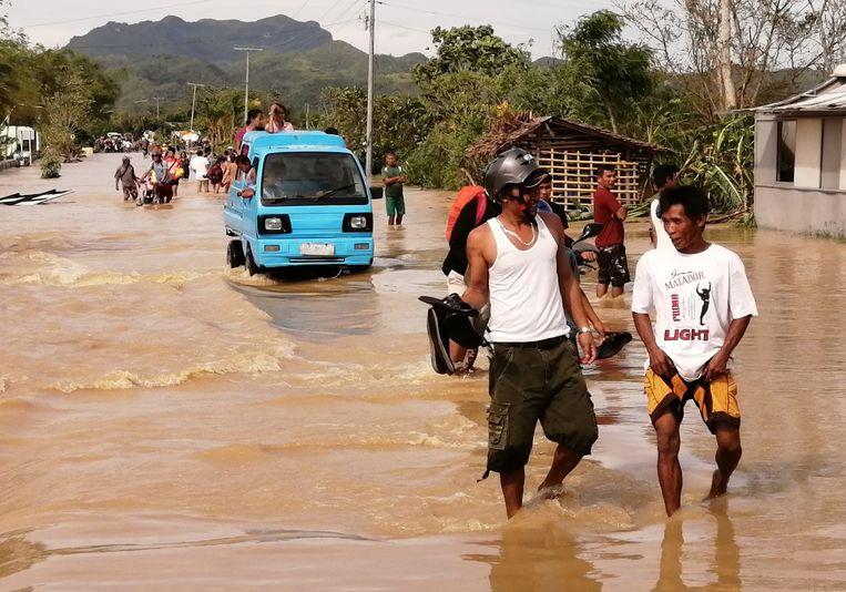 Mensen waden door het water, dat land en huizen overspoelt. Beeld EPA