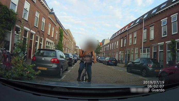 De appende vrouw op de fiets, vlak voor ze tegen de auto botst.