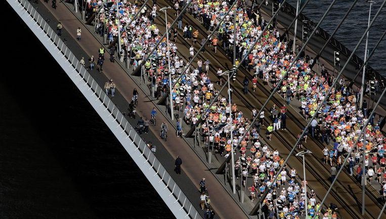 Deelnemers aan de marathon van Rotterdam lopen zondag over de Erasmusbrug in Rotterdam. Beeld anp