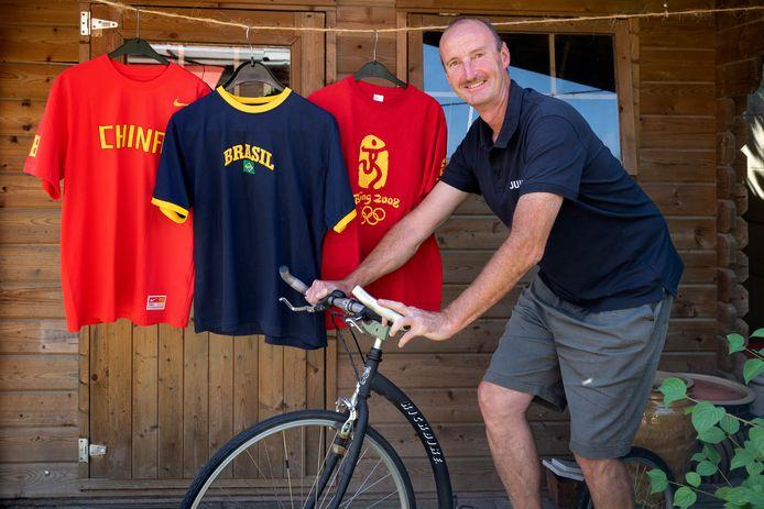 Leo Janssen met een speciale step waarmee hij in 2004 vanuit Empel naar Athene reed. Op de achtergrond truien die herinneren aan zijn bezoek aan meerdere Olympische Spelen.