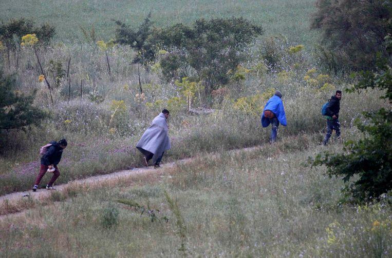 Een groep mannen rent weg om te voorkomen dat ze worden geëvacueerd naar een ander kamp. Beeld null