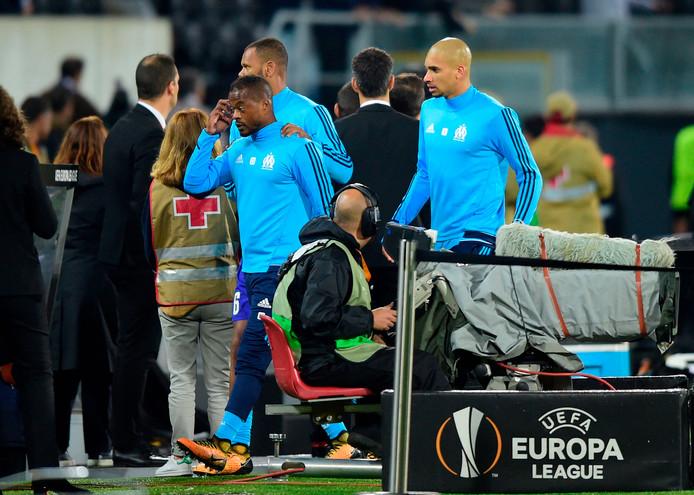 Patrice Evra wordt naar de kleedkamer begeleid na het incident met de Marseille-fans.