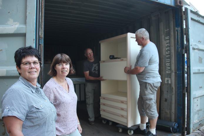 Dymphie Theijssen (links) en Monique van den Broek met hun mannen bij de container voor Tanzania.