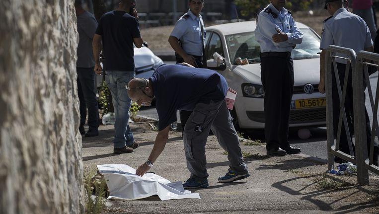 Het Palestijnse slachtoffer van een steekpartij ligt in Jeruzalem op straat. Beeld getty