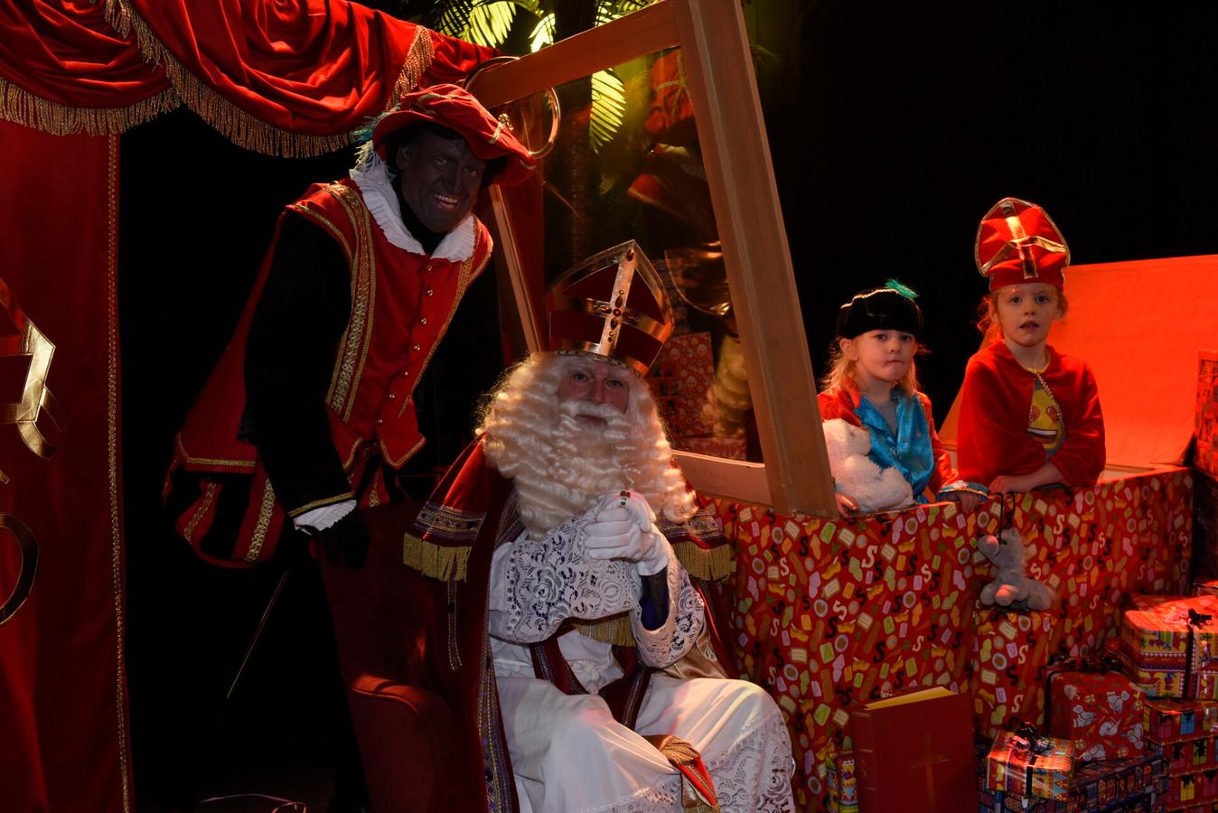 Eline (3) en Jana (5) gaan op de foto met Sinterklaas, die voor de zekerheid poseert achter het plexiglas.