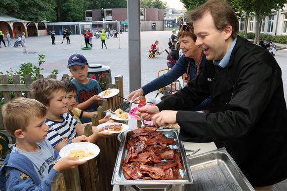 Burgemeester Lieven Janssens en schepen Mizel Gebruers serveren spek met eieren aan de kinderen in de Knipoog.