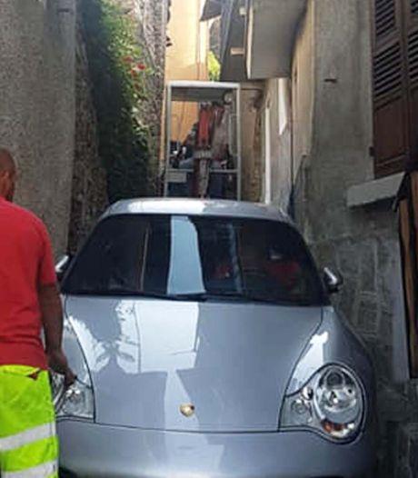 Porsche rijdt zich vast in smal straatje en moet met graafmachine bevrijd worden