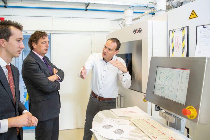 Burgemeester René Verhulst (midden) en wethouder Jan Pieter van der Schans (links) op bezoek bij Oceanz waar directeur Erik van der Garde (rechts) vertelt over de rol bij de bestrijding van corona.