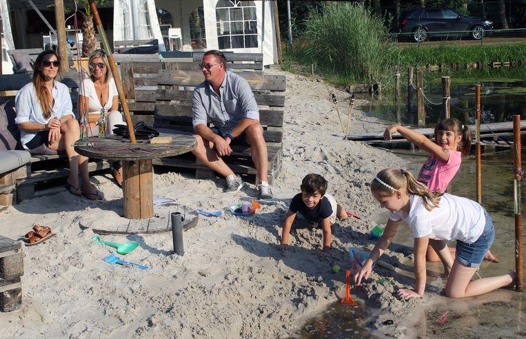 Bezoekers met hun kinderen genieten op het strandje