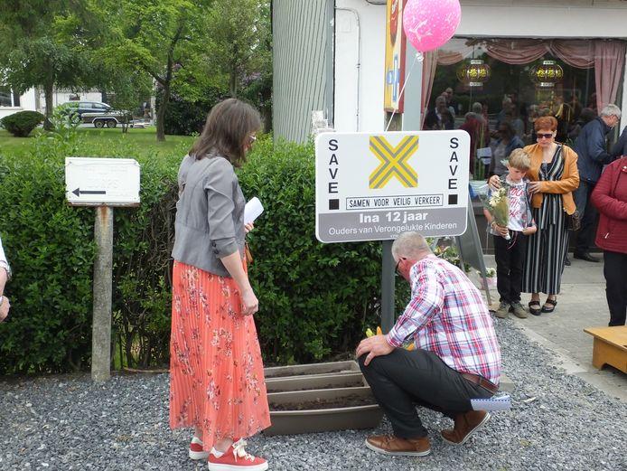 De ouders van Ina leggen bloemen neer bij het SAVE-bord.