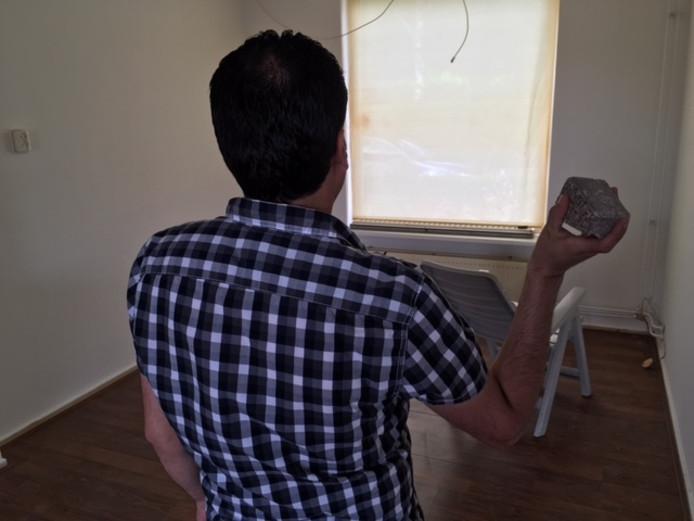 Syriër Shikhmos Shikh Mostafa in het huis waar begin juli deze steen door de ruit vloog.
