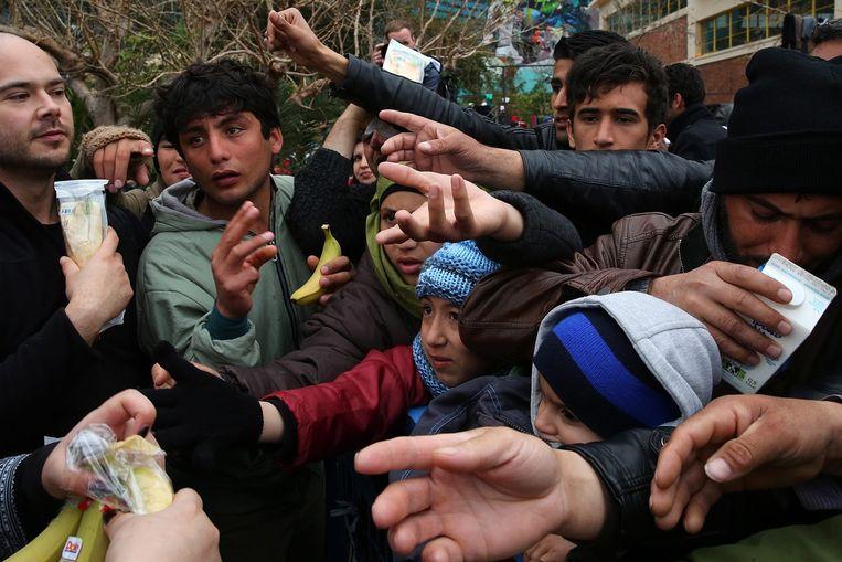 Vluchtelingen bij de Griekse plaats Piraeus krijgen voedsel. Beeld epa