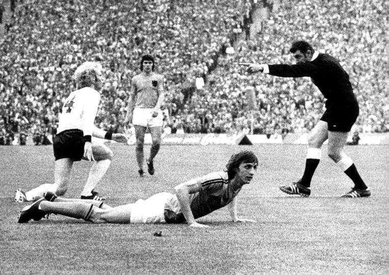 Middenvelder Uli Hoeness (L) haalt Johan Cruyff (onder) neer. De Engelse scheidsrechter John Taylor (R) ziet het incident tijdens de WK-finale (1974) tussen Nederland en West-Duitsland. Beeld anp
