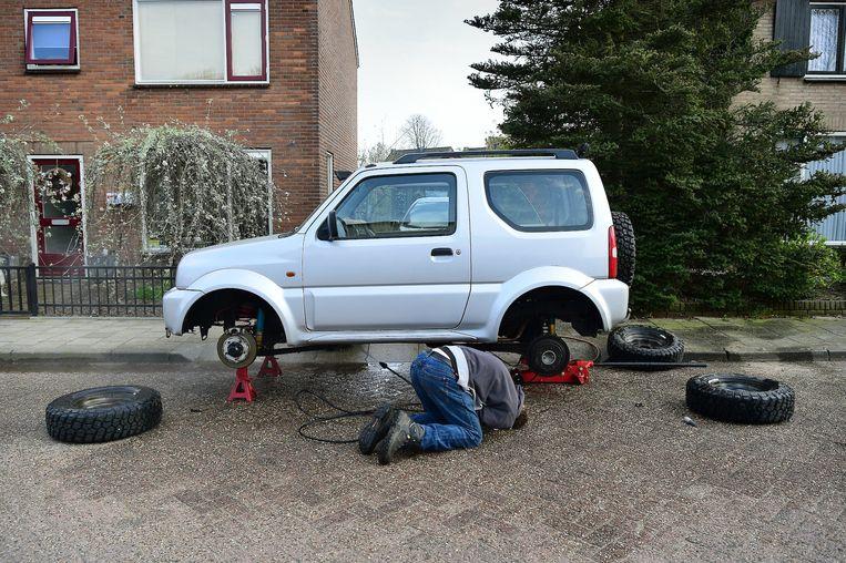 Een man in Maasbommel geeft zijn auto eens een grondige schoonmaakbeurt. Beeld Marcel van den Bergh / de Volkskrant