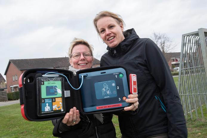 De aed voor de wijk Hambroek in Borculo. Initiatiefneemsters Monique Vastenhout (links) en Melissa Berkemeijer hebben de defibrillator voor elkaar gekregen met een actie.