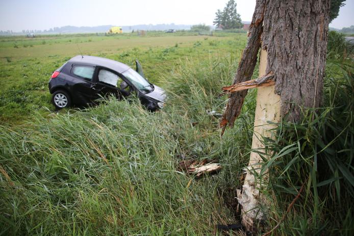 De auto belandt na een botsing met een bom deels in de sloot.